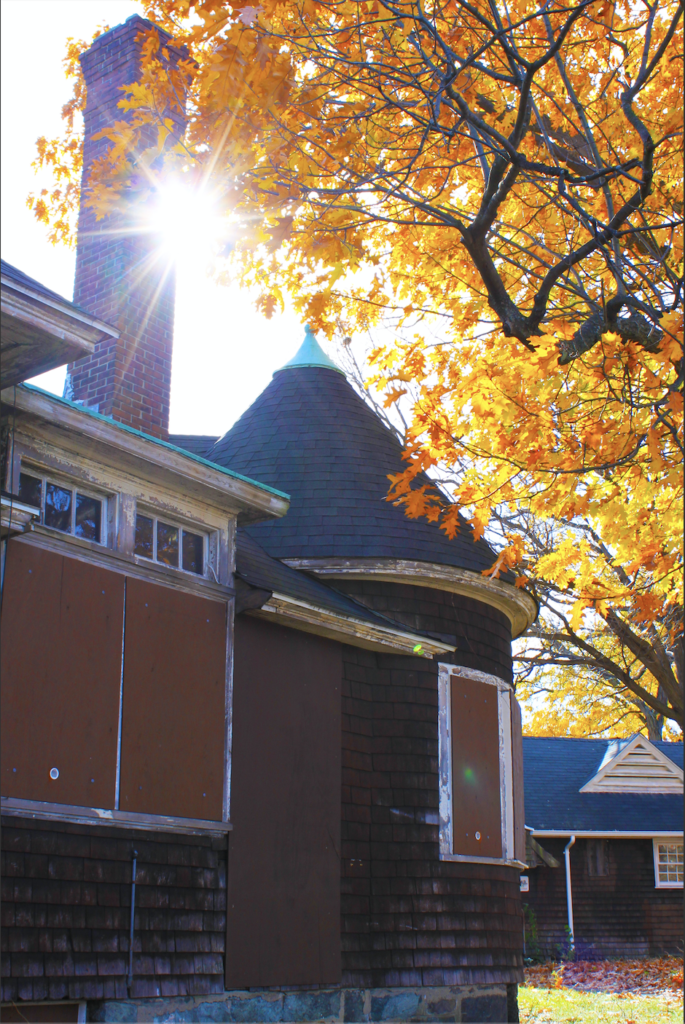 Photograph of the Shingle-style buildings of the Charles River Speedway framed against autumn foliage and sunshine in November 2014. The Architectural Heritage Foundation (AHF) is preserving and redeveloping the Speedway as a mixed-use commercial complex.