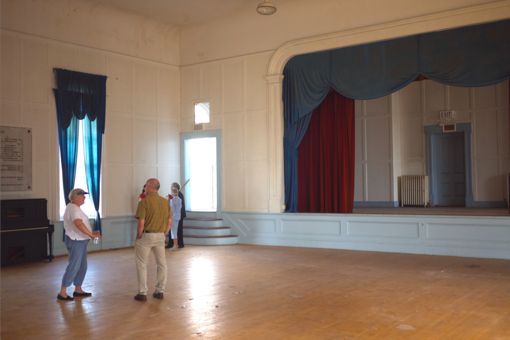 North Brookfield community members stand conversing in the Great Hall of the North Brookfield Town House in front of a stage with blue and red velvet curtains. The Architectural Heritage Foundation (AHF) is providing historic preservation consulting services